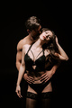 muscular man hugging sexy woman in underwear and stockings isolated on black - PhotoDune Item for Sale