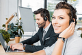 side view of smiling call center operators at workplace in office - PhotoDune Item for Sale