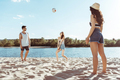 group of active friends playing volleyball on beach together - PhotoDune Item for Sale