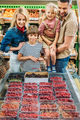 happy young family with two kids choosing berries in supermarket - PhotoDune Item for Sale