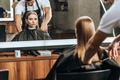 hairstylist cutting hair to beautiful young woman in beauty salon - PhotoDune Item for Sale