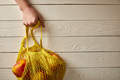 cropped view of female hand with string bag full of rape apples on white wooden surface, zero waste - PhotoDune Item for Sale