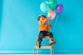cute kid in jeans and orange shirt sitting on stairs and pointing with finger at balloons - PhotoDune Item for Sale