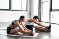 side view of sporty young couple stretching and exercising on yoga mats in gym - PhotoDune Item for Sale