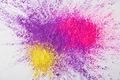 top view of explosion of purple, pink and yellow holi powder on white background - PhotoDune Item for Sale