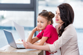 Smiling daughter and mother working with laptop and looking at paper in office - PhotoDune Item for Sale