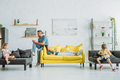 mother and father with two children using smartphones while resting on couches at home - PhotoDune Item for Sale