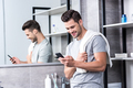 happy young man using smartphone in bathroom - PhotoDune Item for Sale