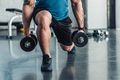 partial view of young sportsman exercising with dumbbells in gym - PhotoDune Item for Sale
