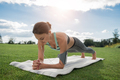 young woman listening music in earphones while practicing yoga dolphin plank pose in park - PhotoDune Item for Sale