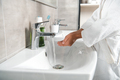 cropped view of man in white bathtub with cupped hands near faucet with water - PhotoDune Item for Sale