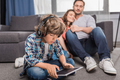 little boy in headphones using tablet with parents resting behind - PhotoDune Item for Sale