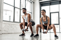 sporty young man and woman squatting with dumbbells in gym - PhotoDune Item for Sale