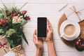 cropped shot of woman holding smartphone with blank screen at surface with wrapped bouquet of - PhotoDune Item for Sale