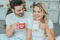 laughing young couple with cups of cocoa sitting in bed at home on christmas - PhotoDune Item for Sale