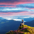 A tourist sits on the edge of a cliff - PhotoDune Item for Sale