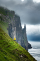 Tourist with backpack in yellow jacket looks at Witches Finger cliffs - PhotoDune Item for Sale