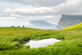 Lonely tourist near small lake looks at foggy islands in Atlantic ocean - PhotoDune Item for Sale