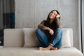 Happy brunette nice girl smiling while sitting on sofa at home - PhotoDune Item for Sale
