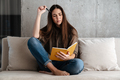 Brooding brunette nice girl writing down notes while sitting on sofa - PhotoDune Item for Sale