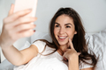 Happy nice girl smiling while taking selfie on mobile phone - PhotoDune Item for Sale