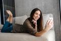 Joyful brunette nice girl smiling while taking selfie on mobile phone - PhotoDune Item for Sale