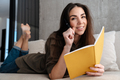 Happy brunette nice girl writing down notes while lying on sofa - PhotoDune Item for Sale