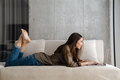 Cheerful brunette nice girl smiling and using laptop while lying on sofa - PhotoDune Item for Sale