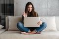 Cheerful brunette nice girl waving hand while using laptop on sofa - PhotoDune Item for Sale