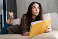 Thinking brunette nice girl writing down notes while lying on sofa - PhotoDune Item for Sale