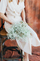 An unrecognizable woman in a beige dress holds a delicate bouquet of gypsophila. - PhotoDune Item for Sale
