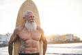 Tattooed senior surfer holding vintage surf board on the beach at sunset - PhotoDune Item for Sale