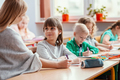Happy children sit together at the table during the first physics lesson in the new school year - PhotoDune Item for Sale