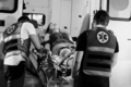 Black and white photo of female young victim of the accident lies on a stretcher in an ambulance - PhotoDune Item for Sale