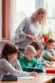 Young blonde haired teacher with children in the classroom - PhotoDune Item for Sale