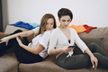 Girls sitting on couch in phone back to back - PhotoDune Item for Sale