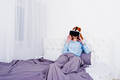 Red haired girl in bed with vr glasses at studio room. - PhotoDune Item for Sale