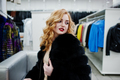Elegance blonde girl in fur coat at the store of fur coats and leather jackets. - PhotoDune Item for Sale