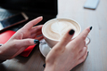 Close up hands of girl with cup of cappuccino background red laptop and mobile phone. - PhotoDune Item for Sale