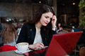 Brunette girl sitting on cafe and  working with red laptop. - PhotoDune Item for Sale