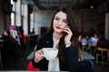 Brunette girl sitting on cafe with cup of cappuccino and speaking mobile phone. - PhotoDune Item for Sale