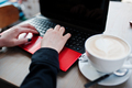 Close up hands of girl working with red laptop with cup of cappuccino. - PhotoDune Item for Sale