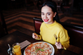 Funny brunette girl in yellow sweater eating pizza at restaurant. - PhotoDune Item for Sale