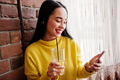 Funny brunette girl in yellow sweater drinking juice and looking at mobile phone at restaurant. - PhotoDune Item for Sale