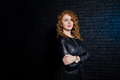 Curly hair girl at leather jacket on studio against black brick wall. - PhotoDune Item for Sale