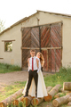 The bride and groom are standing on the logs and hugging against the background of an old barn. - PhotoDune Item for Sale