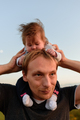 A little cute daughter sits on her neck near her father. - PhotoDune Item for Sale