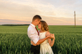 Bride and groom in a wheat field. A couple is hugging during sunset. - PhotoDune Item for Sale