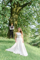 The bride and groom are hugging on the background of a green park. - PhotoDune Item for Sale