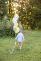 A boy of primary school age runs with balloons. The boy is pointing his back to the camera. - PhotoDune Item for Sale